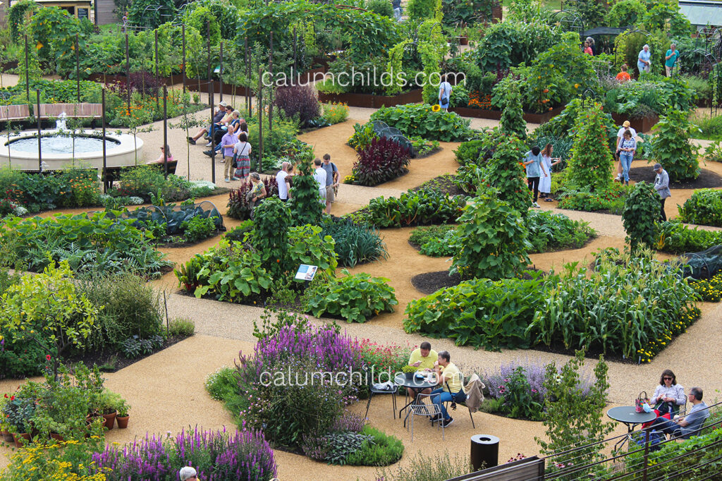 An aerial view of a large green garden with multiple people sitting at silver tables scattered around the image.