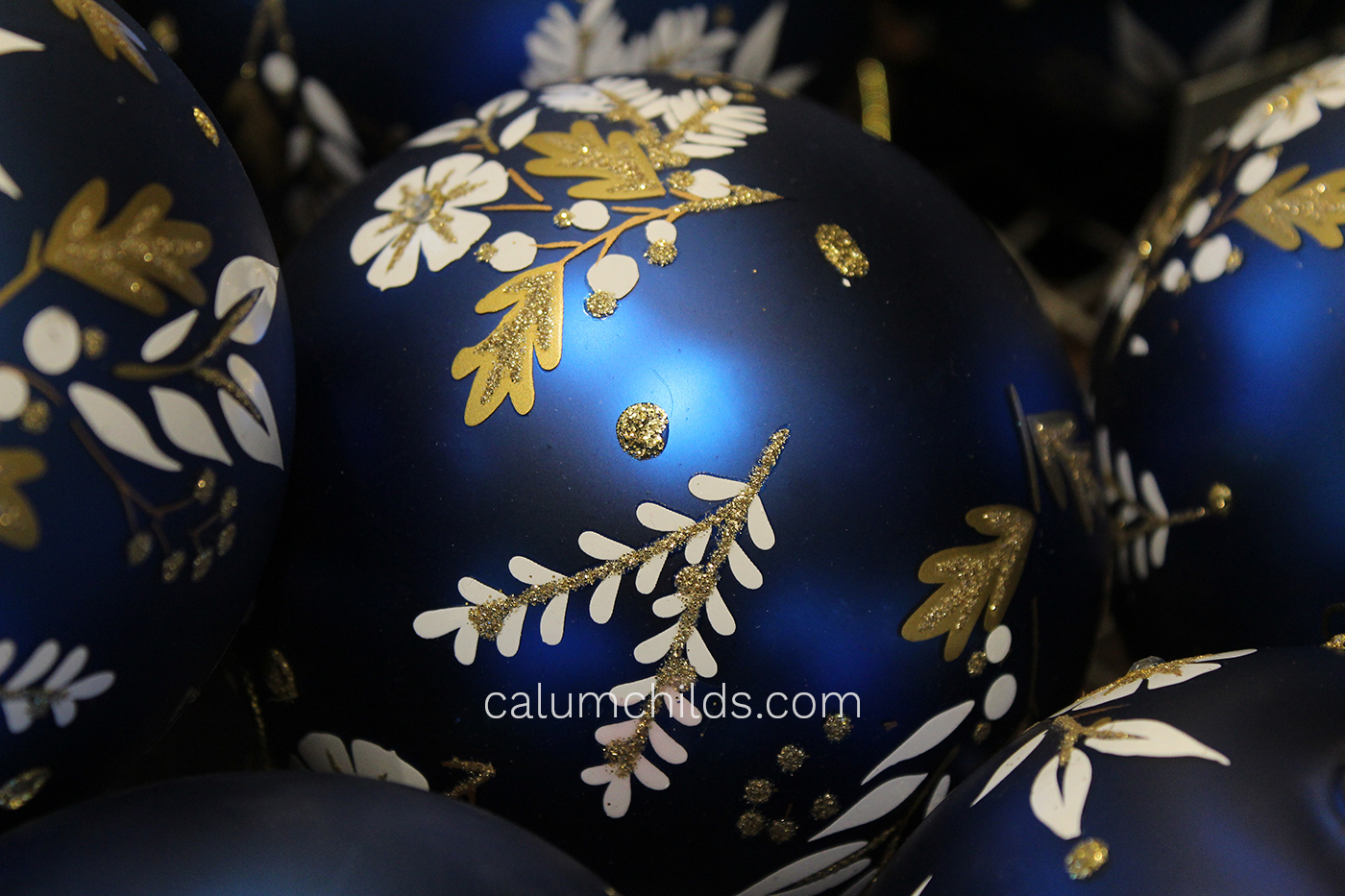A blue bauble decorated with gold glitter and leaf-shaped paper.