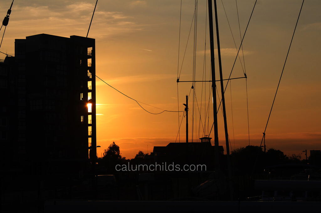 The yellow light of the sun lights up an apartment building with sails of a yacht.