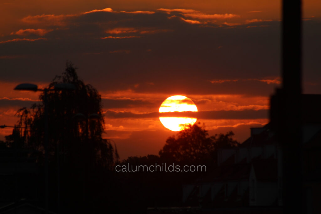 The bright yellow sun sets on a dark red/orange sky with the shadows of trees and clouds.