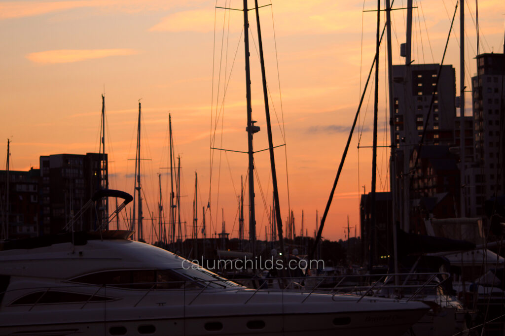 The shadows of sails and apartment buildings create a backdrop to the orange/red sky.