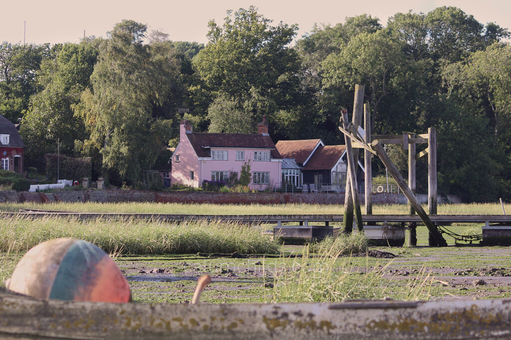 A pink detached house in the foreground surrounded by large green trees with marshland and a ball inside a canoeing boat in the foreground.