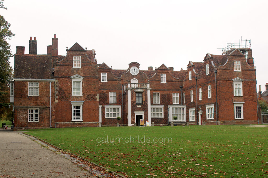 A wide shot of the Christchurch Mansion (made out of bricks with white frame windows and a clock in the middle) and some of the lawn in front of it.