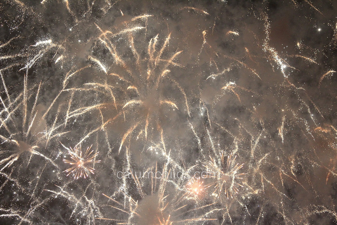 Gold fireworks explode in the sky, with smoke being emitted from all angles.
