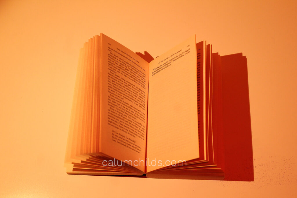 An open book with the shadows a dark red.