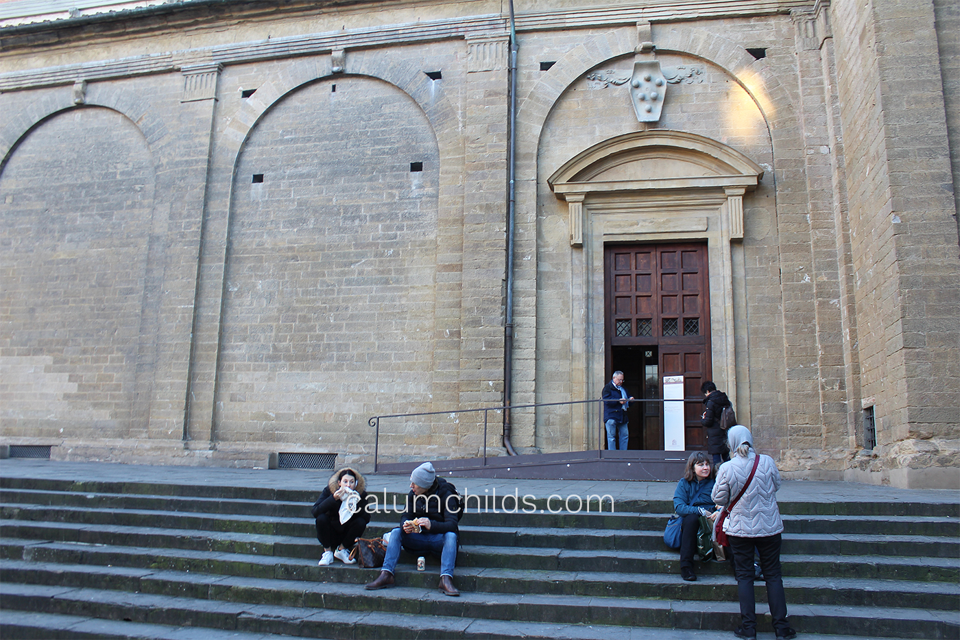 People wait outside a large stone building.