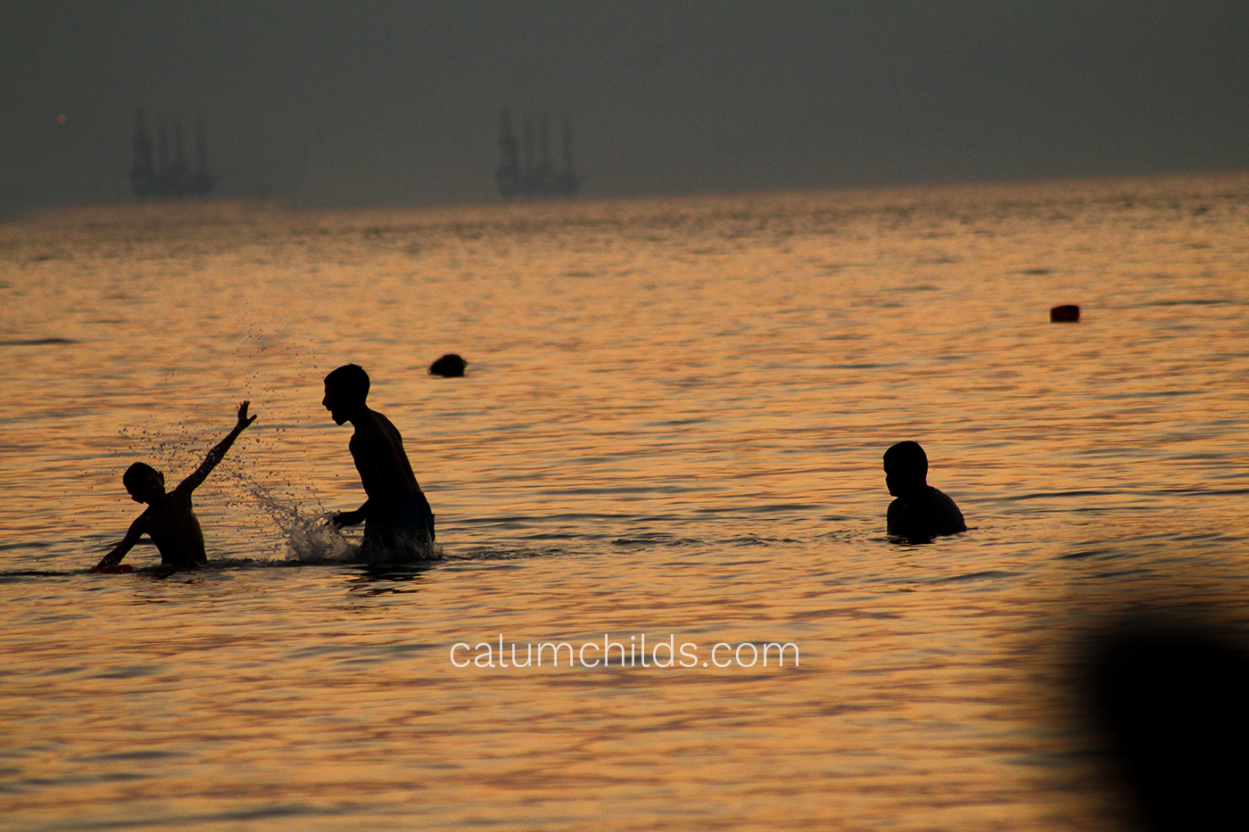 Three people (silhouettes) playing in the sea.