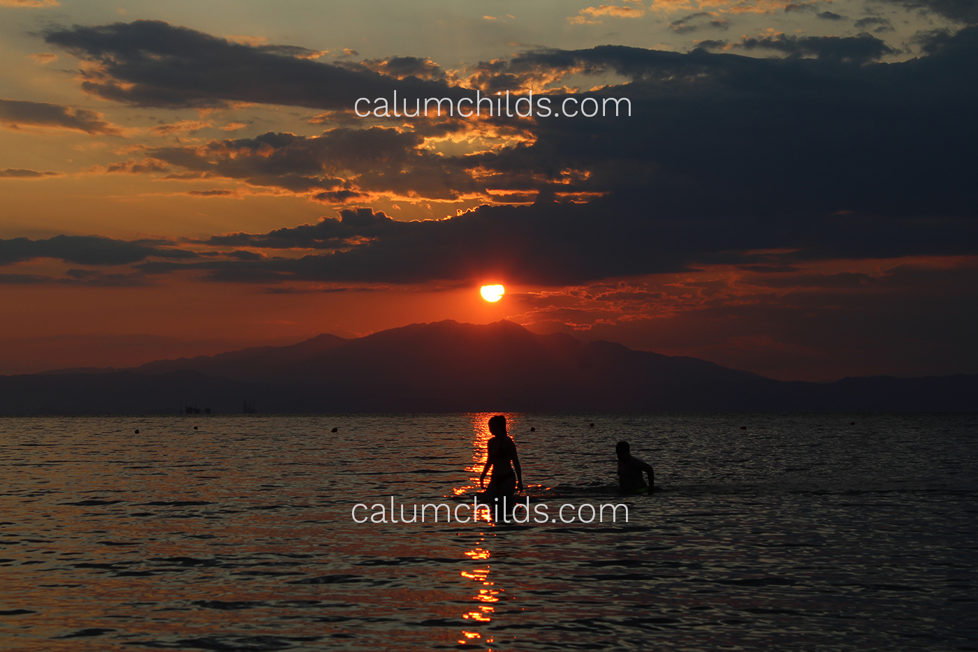 A person walks through the orange beam the sun is creating on the sea, surrounded by large mountains.