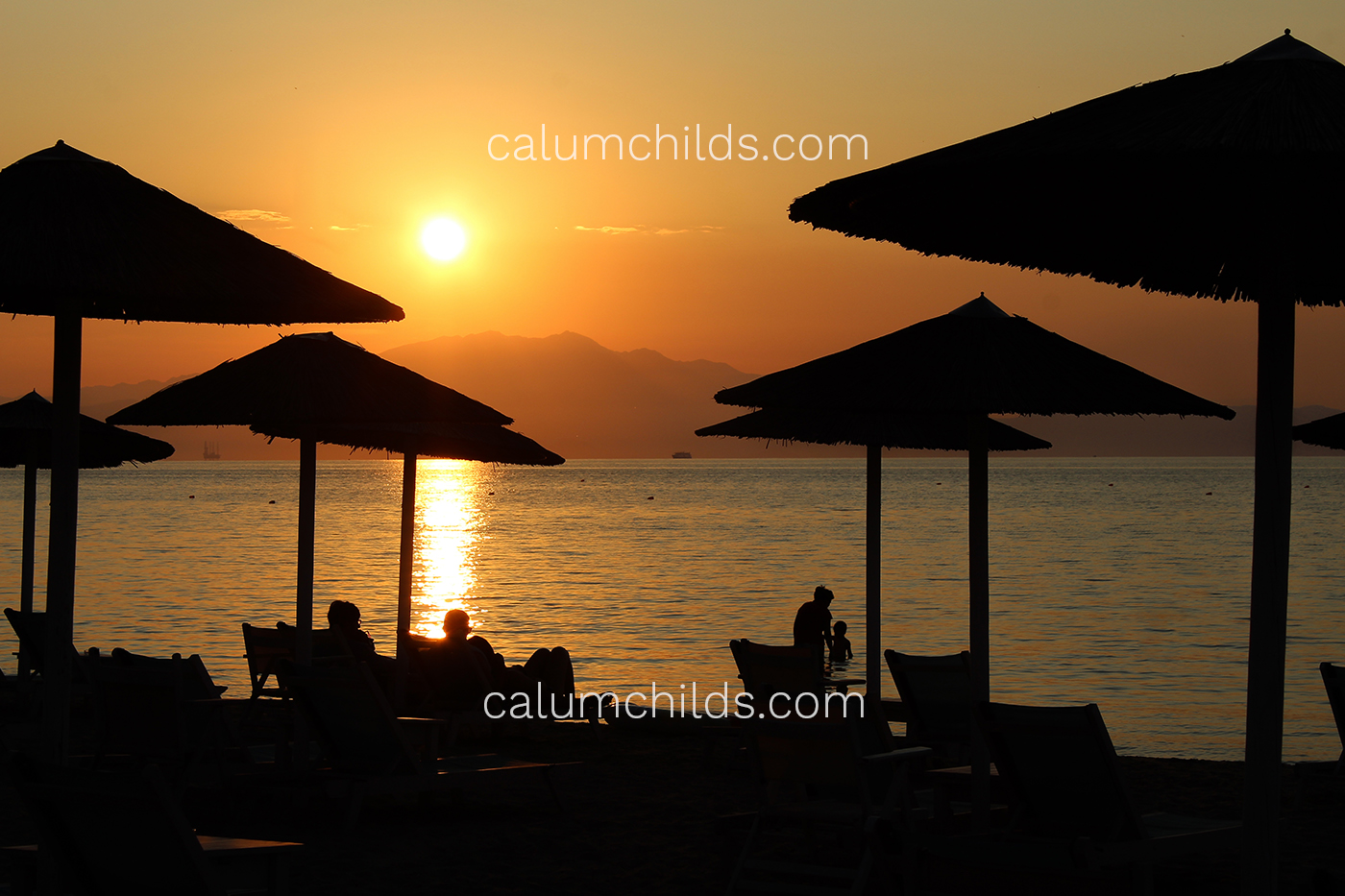 Multiple umbrellas and people sitting on sunbeds in the foreground, with a sunset in the background.