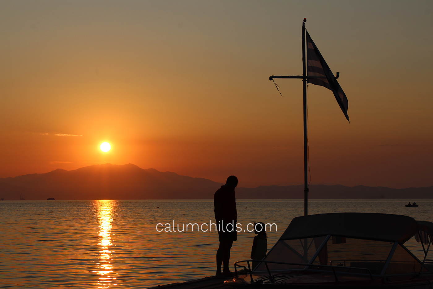 An adult and a child stand beside a boat, with a Greek flag hanging on a pole in front of them. To the left of them is an orange sun.